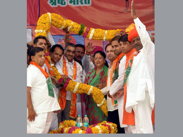 Vasundhara Raje & BJP candidate Hariom Singh being garlanded at an election rally