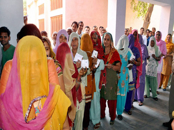 Women show their voting ID card