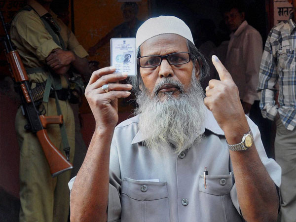 A Muslim voter shows his voter ID card