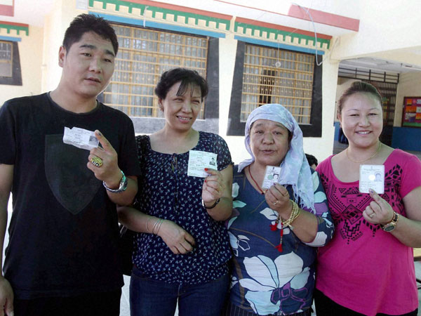 Tibetans show their voter ID card