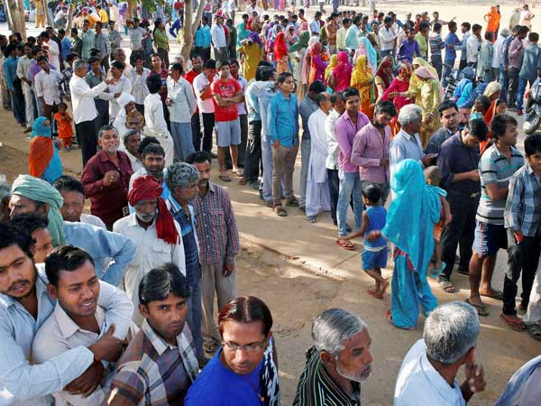 Voters stand in queues to cast their votes