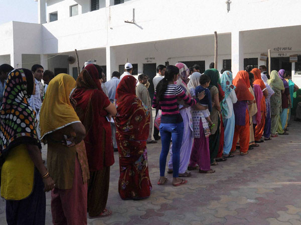 Voters stand in queue to cast their votes