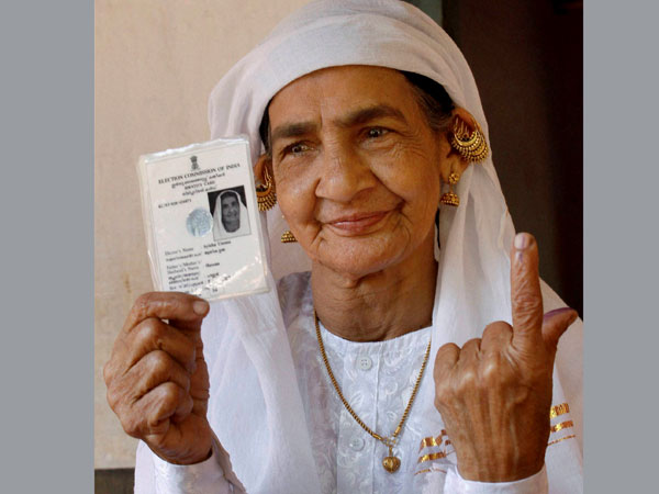A woman shows her finger after casting the vote
