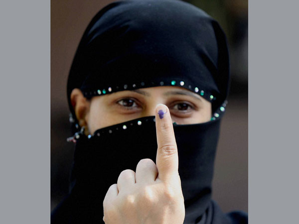 A muslim woman shows ink marked finger