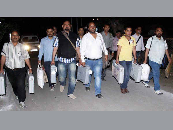 Polling officials carry electronic voting machines (EVM)