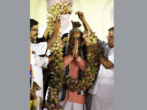 Narendra Modi being garlanded at an election rally