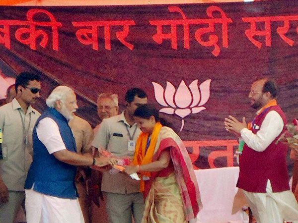 Narendra Modi is greeted at an election campaign rally