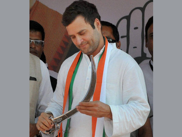 Rahul Gandhi holds a sword during an election rally