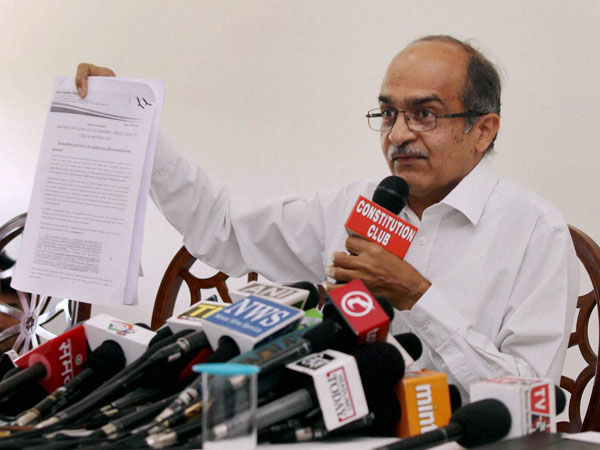 AAP leader Prashant Bhushan shows a document