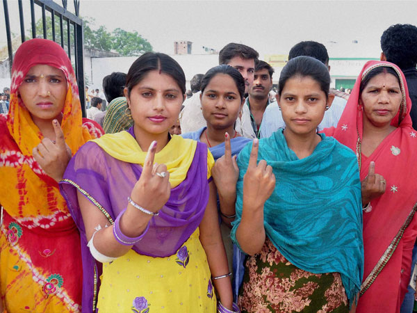 Women voters show their inked fingers after casting votes