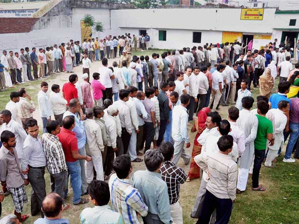 Voters stand in queue to cast their vote for Lok Sabha elections