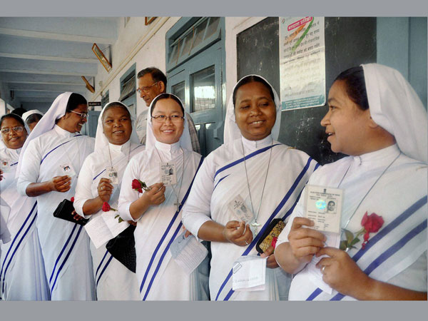 Catholic nuns wait in a queue to cast their votes