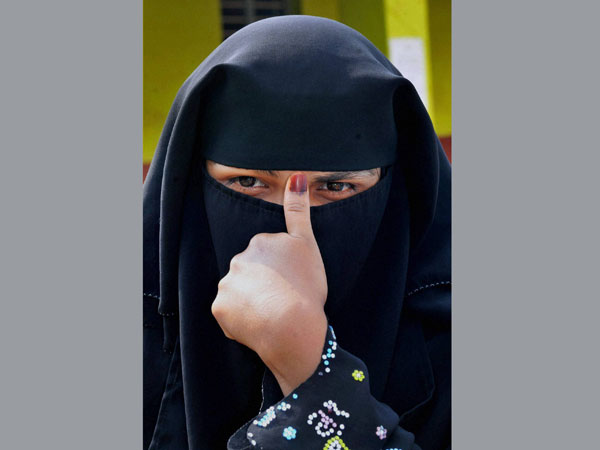 A Muslim woman shows her inked thumb