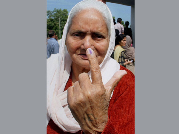 An elderly woman shows her inked finger