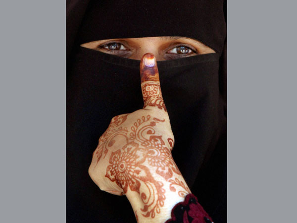 A burqa-clad woman shows her inked thumb