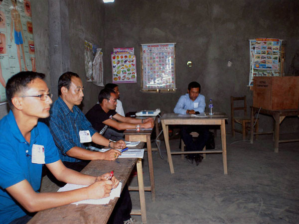Polling officials sitting idle at a polling station as villagers