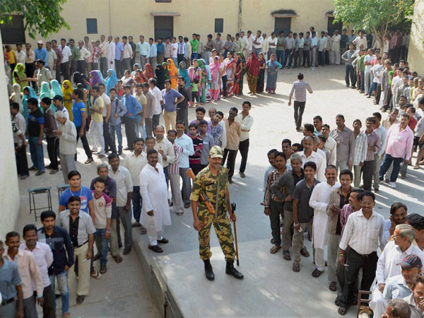 Voters wait in queues to cast their votes