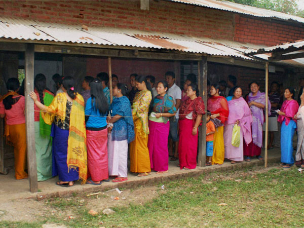 Women wait in queue to cast their votes for Lok Sabha elections