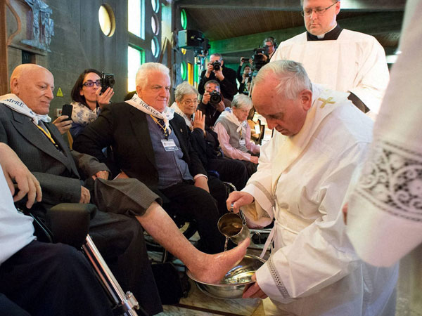 Pope Francis washes the foot of a man
