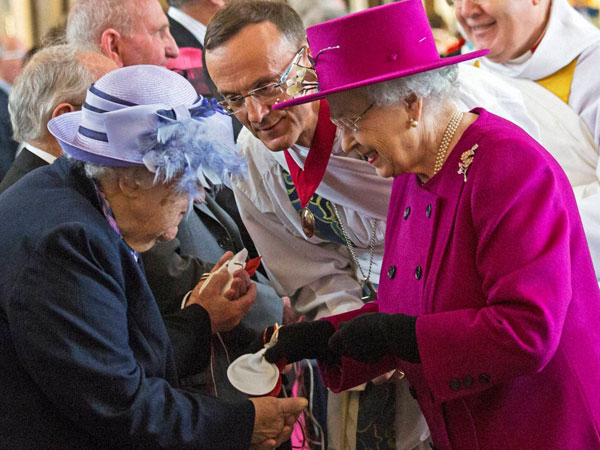 Britain's Queen Elizabeth II right, reacts with pensioner Mrs Bradshaw
