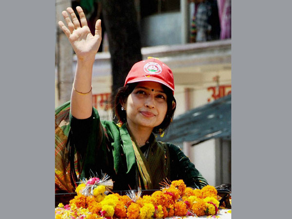 Dimple Yadav waves to the supporters during a roadshow