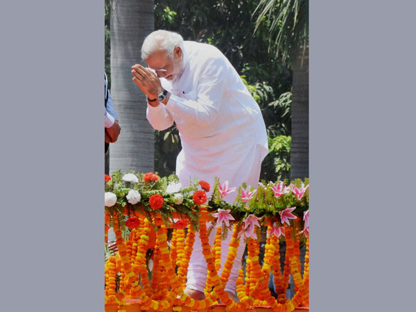 Narendra Modi greets supporters at a road show