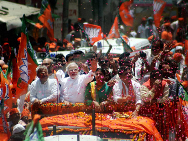 Narendra Modi waves at supporters during a road show