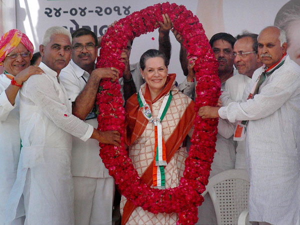 Sonia Gandhi is garlanded at an election rally at Kheralu