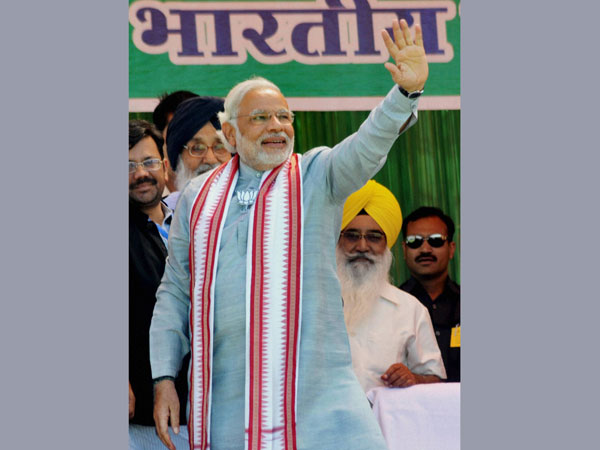 Narendra Modi waves at supporters during an election rally