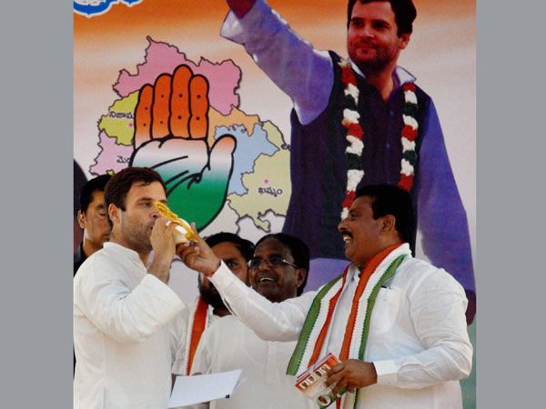Rahul Gandhi blows a conch at a public meeting during an election campaign