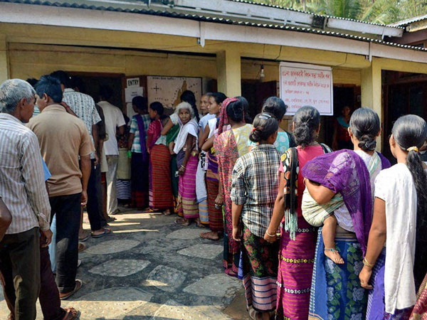 People stand in queue to cast their vote