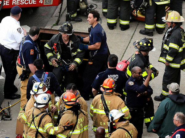 New York City firefighters emerge from a hatch in the sidewalk