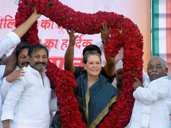 Sonia Gandhi is garlanded by supporters during an election campaign