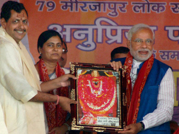 Narendra Modi is presented a memento at an election rally