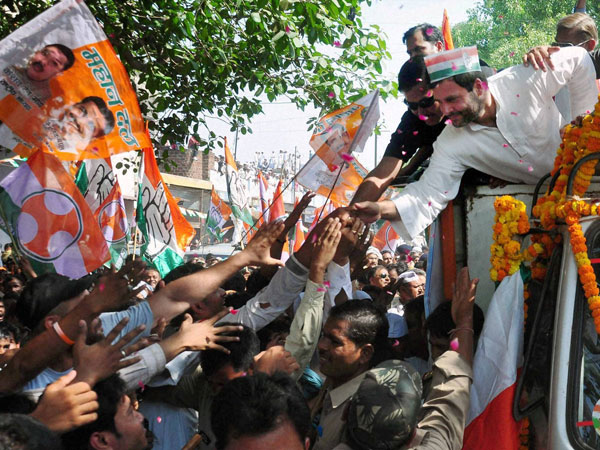 Rahul Gandhi shakes hands with supporters during an election road show