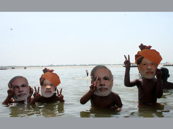 Children take bath wearing masks of BJP Prime Ministerial candidate Narendra Modi