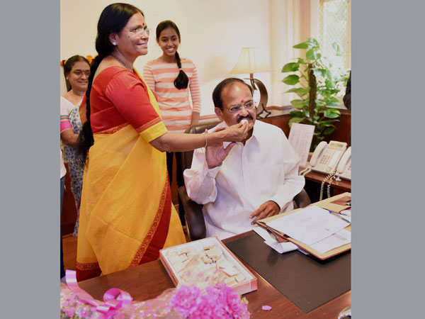 M Venkaiah Naidu being offered sweets by his wife M. Ushamma