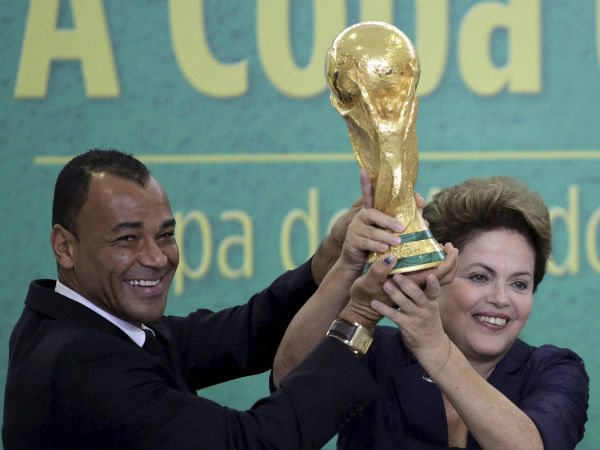 Former Brazilian soccer player Cafu and Brazil's President Dilma Rousseff lift the 2014 World Cup trophy after it was officially presented to Rousseff by FIFA President Sepp Blatter at a ceremony at the Planalto presidential palace, in Brasilia, Brazil, on June 2, 2014