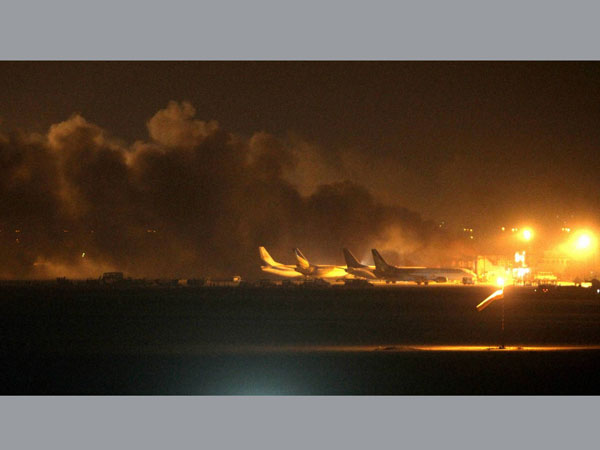 Fire illuminates the sky above Karachi airport terminal where security forces are fighting with attackers Sunday night, June 8, 2014, in Pakistan. Gunmen disguised as police guards attacked the terminal with machine guns and a rocket launcher during a five-hour siege that killed 13 people as explosions echoed into the night, while security forces retaliated and killed all the attackers, officials said Monday.