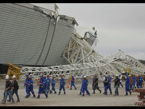 File photo (December, 2013): Construction workers walk past the damage caused by the collapse at the Corinthians Arena stadium that will host the opening match of the World Cup