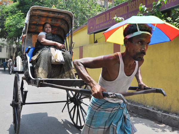A rickshaw puller with an umbrella on a hot day in Kolkata