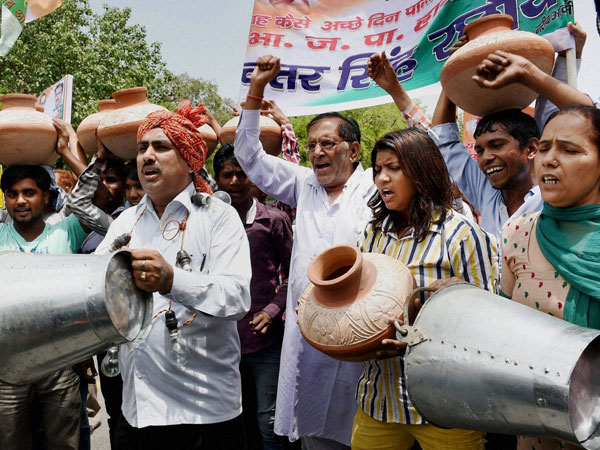 Protesters carry pitchers and buckets during a protest