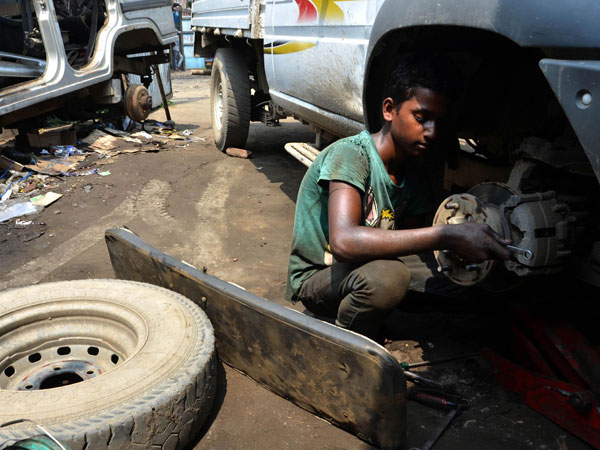 A boy works on a car at a vehicle repair garage