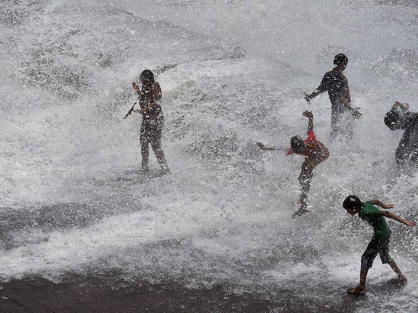 People enjoy high tide at Marine drive in Mumbai