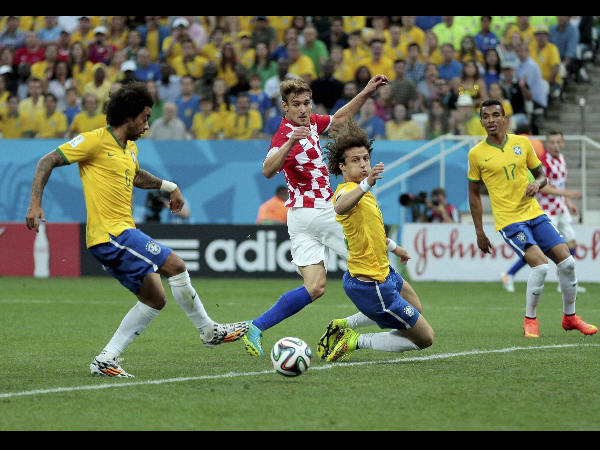 Brazil's Marcelo, left, tries to clear the ball but scores on his own goal
