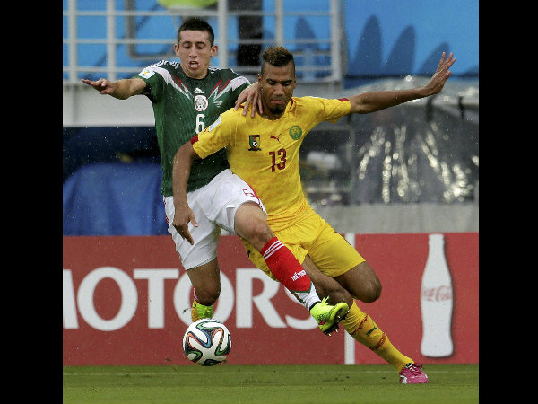 Mexico's Hector Herrera (6) challenges Cameroon's Maxim Choupo-Moting (13) for the ball during the first half the group A World Cup match