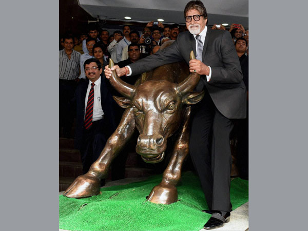 Bollywood actor Amitabh Bachchan poses with the bull statue