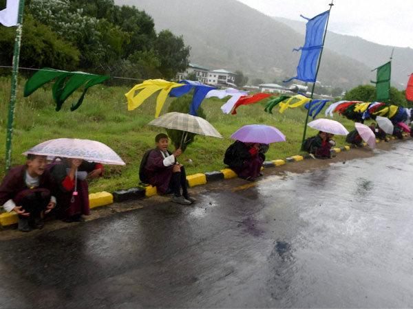 Children wait with umbrellas in rains to bid goodbye