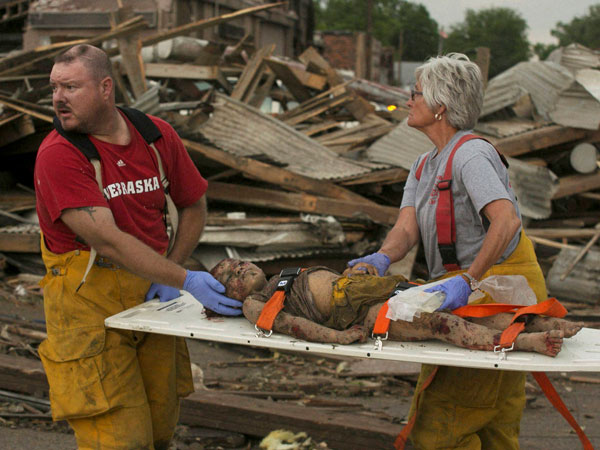 Rescue personnel tend to a young tornado victim
