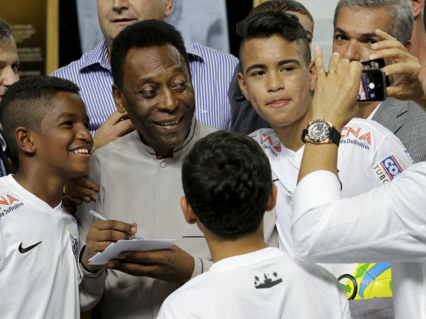 Pele pose for a photo next to young players of the Santos soccer team during the inauguration of the Pele Museum in Santos, Brazil, Sunday, June 15, 2014. The Pele Museum exhibits his personal collection, pictures, films, trophies and printed material about his history as a soccer player and personality.